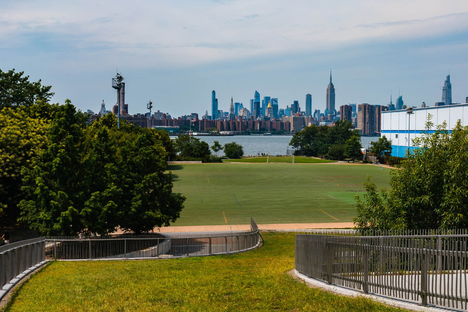 lawn and NYC skyline view from Marsha P Johnson Park formerly East River State Park in Williamsburg Brooklyn