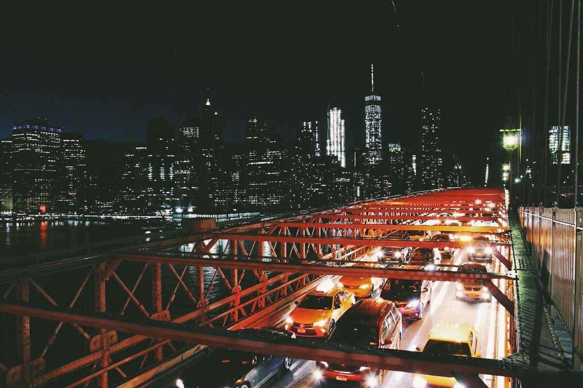 NYC-city-skyline-and-cars-on-brooklyn-bridge-at-night-by-katie-hinkle