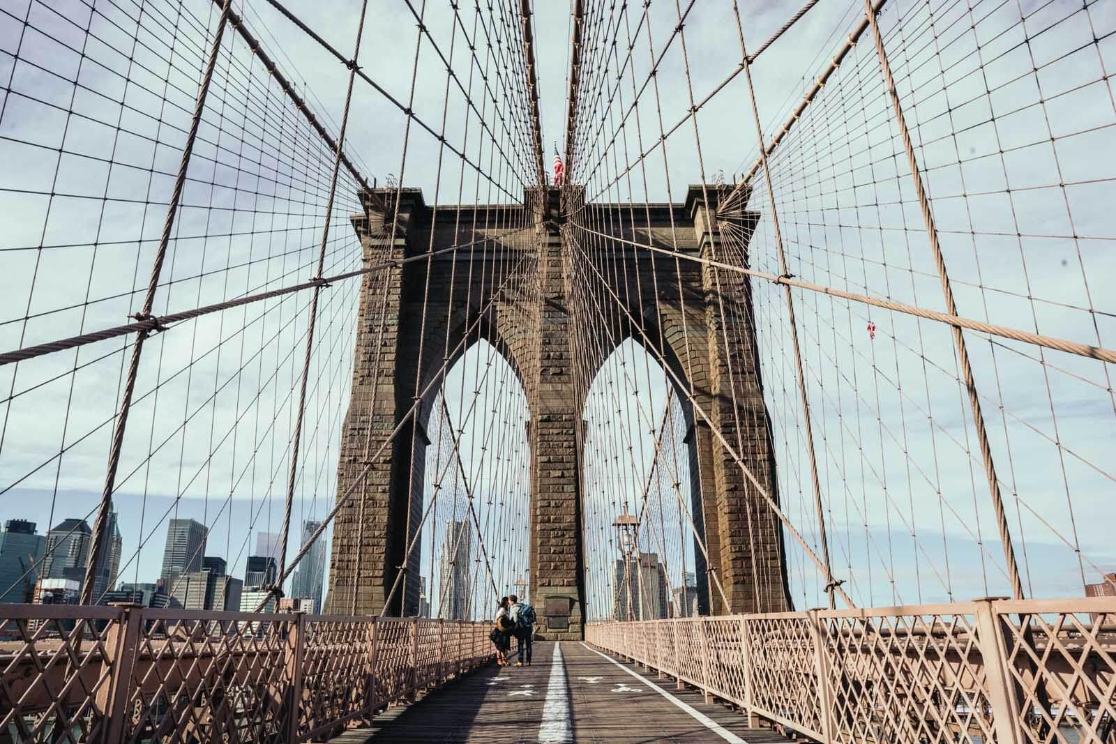 a couples kiss on the Brooklyn Bridge