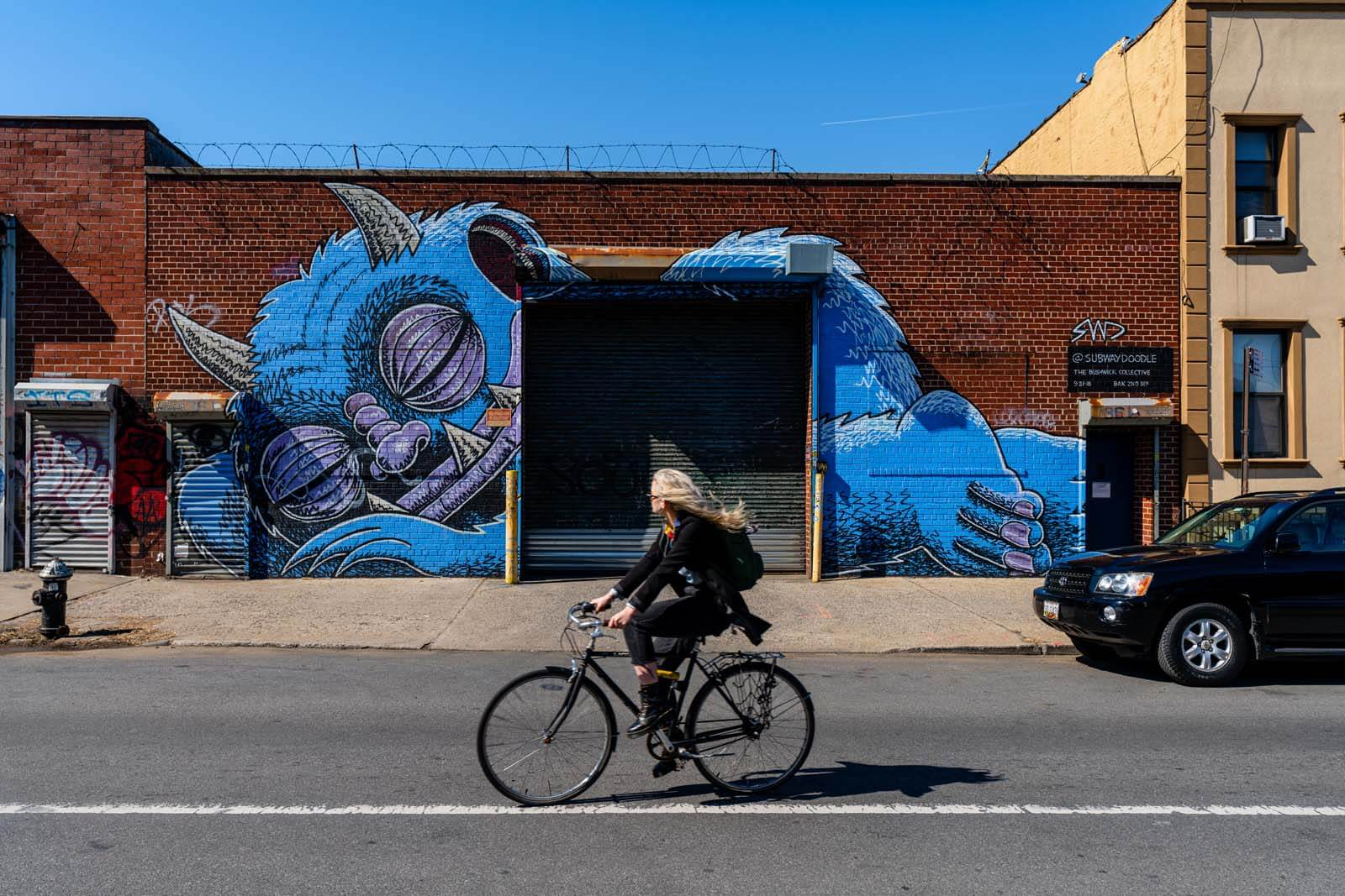 sleeping monster in Bushwick Brooklyn mural and cyclist