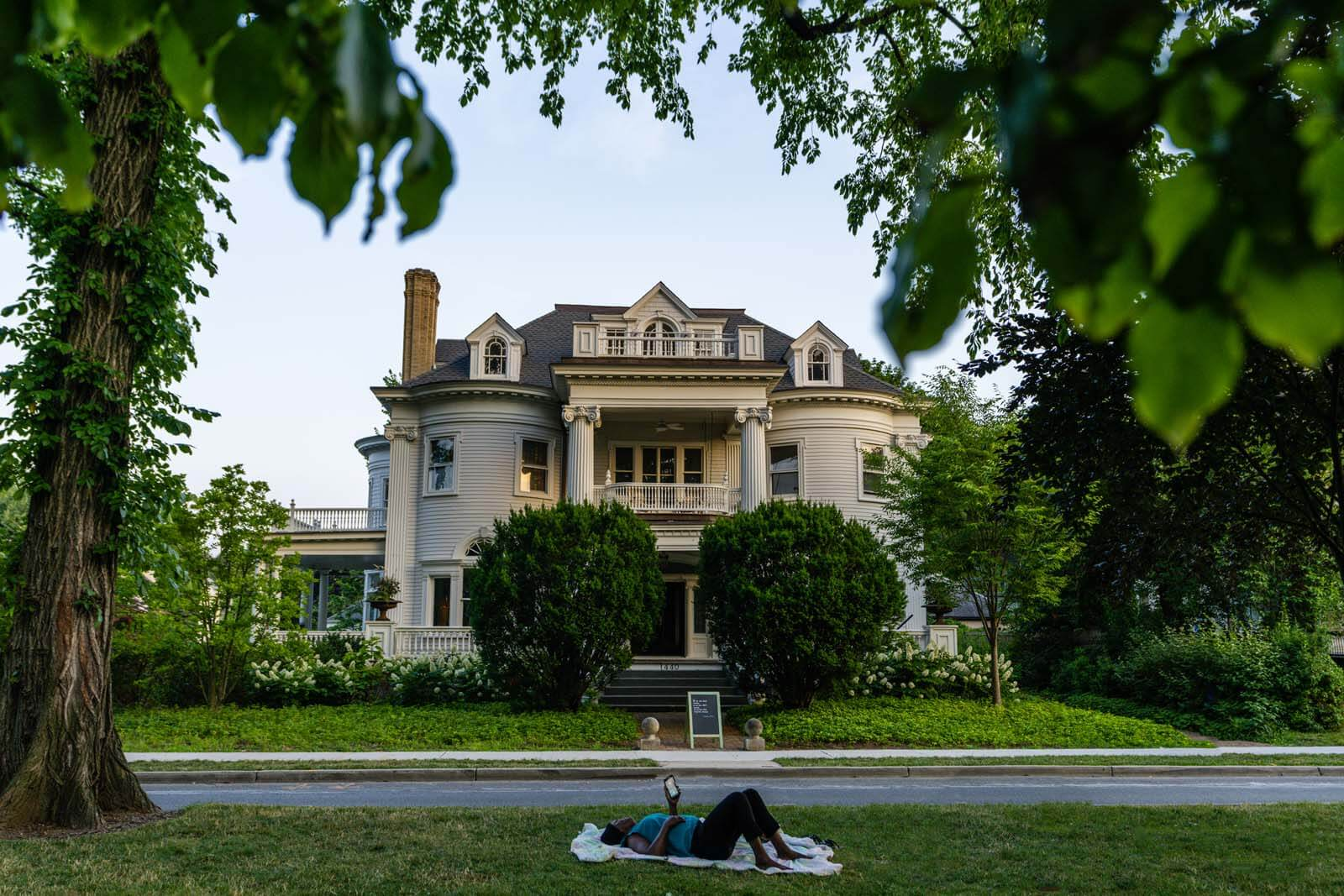 Woman relaxing on Flatbush Mall in front of big beautiful home