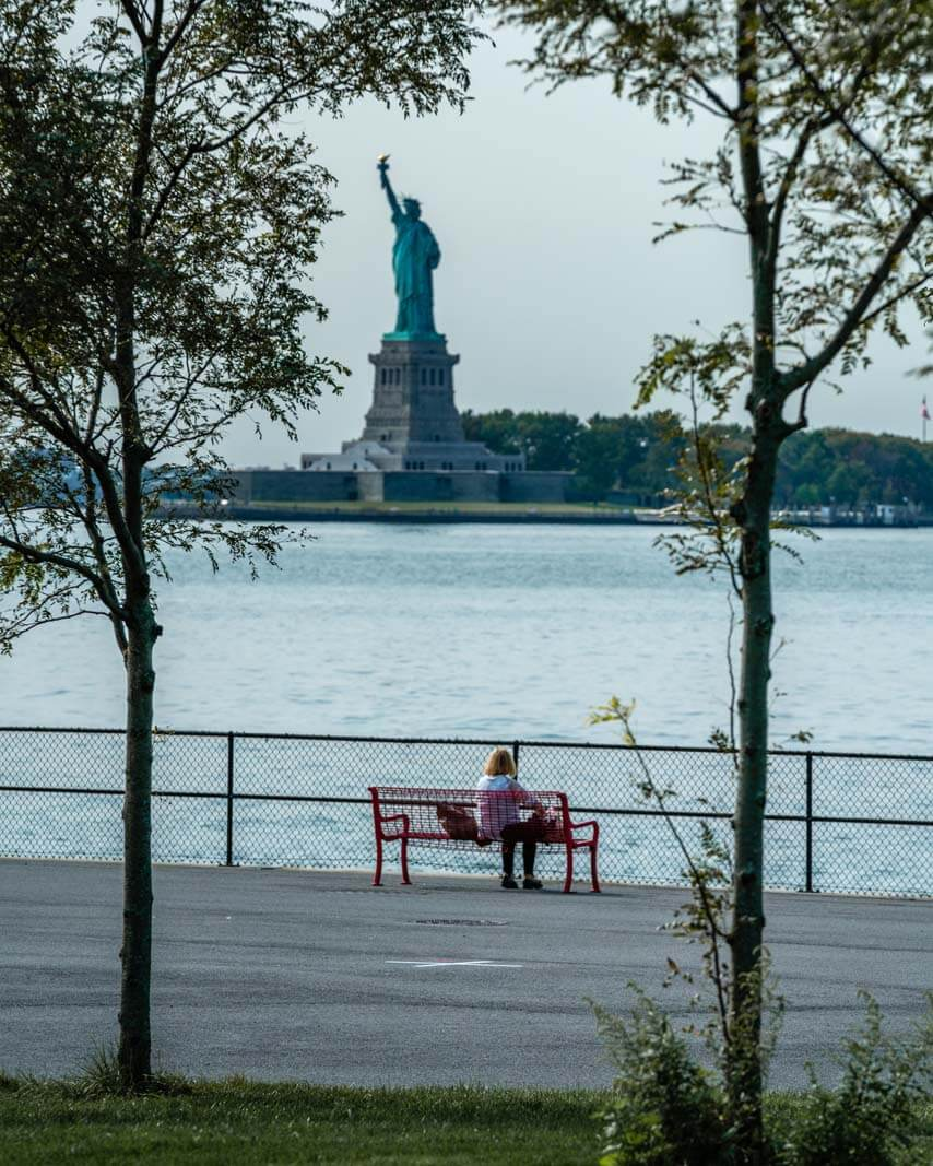 lady on a bench at Governors Island looking at the Statue of Liberty