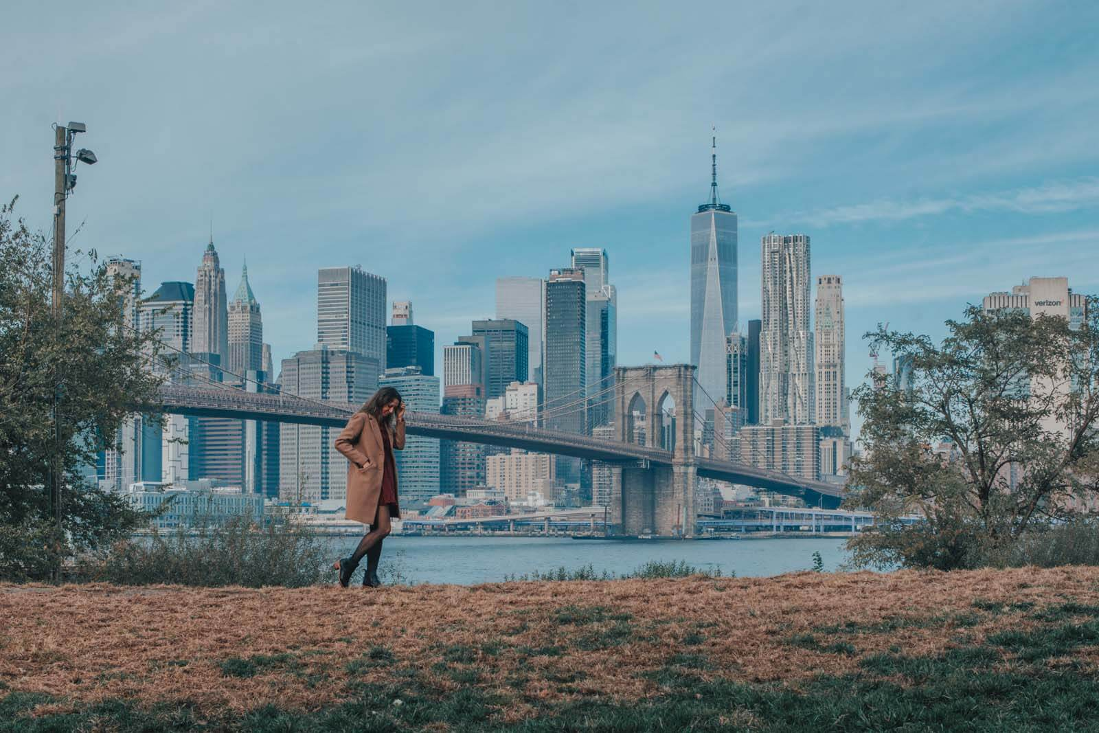 Girl walking by Brooklyn Bridge with skyline view in Brooklyn Bridge Park