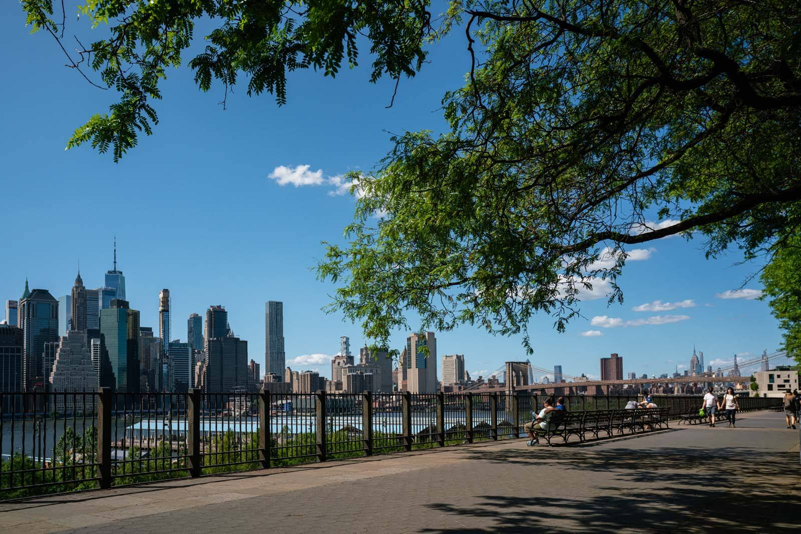 People sitting on a bench and looking at Manhattan from the Brooklyn Heights Promenade