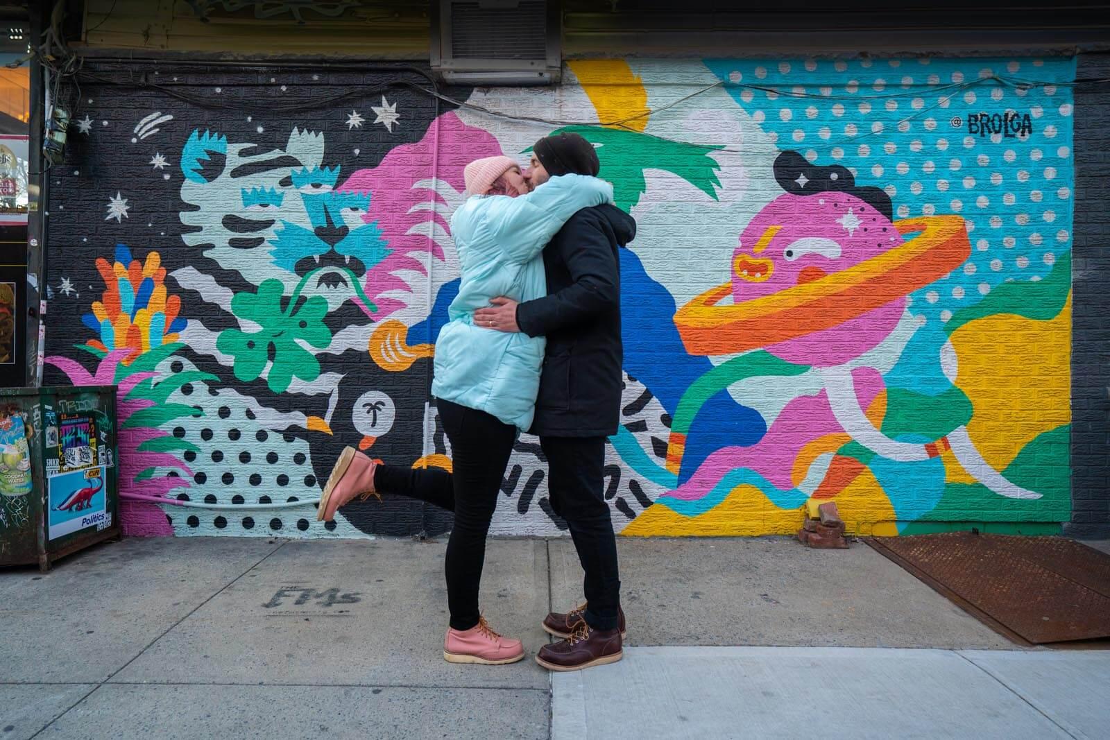 kissing in front of the Brolga mural in Williamsburg Brooklyn