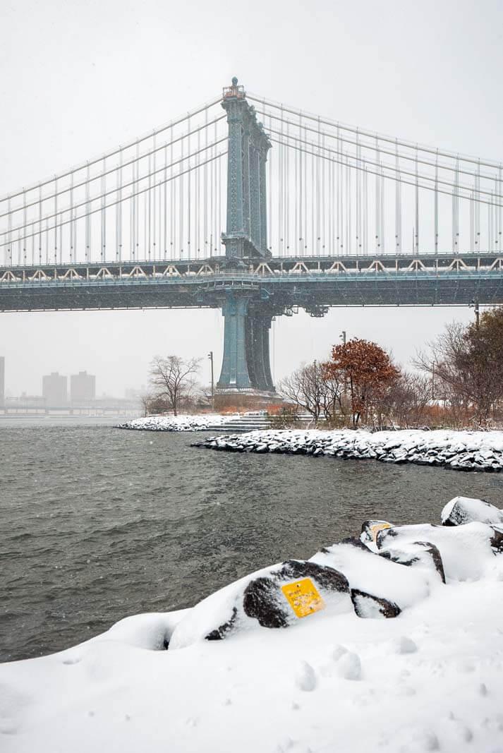 view of Manhattan Bridge in the snow at Brooklyn Bridge Park in DUMBO