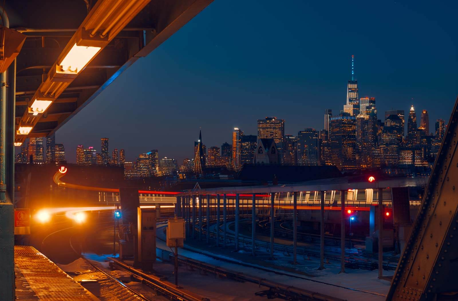 F Train Arriving at Smith and 9th Station with Brooklyn and Manhattan Skyline in Distance