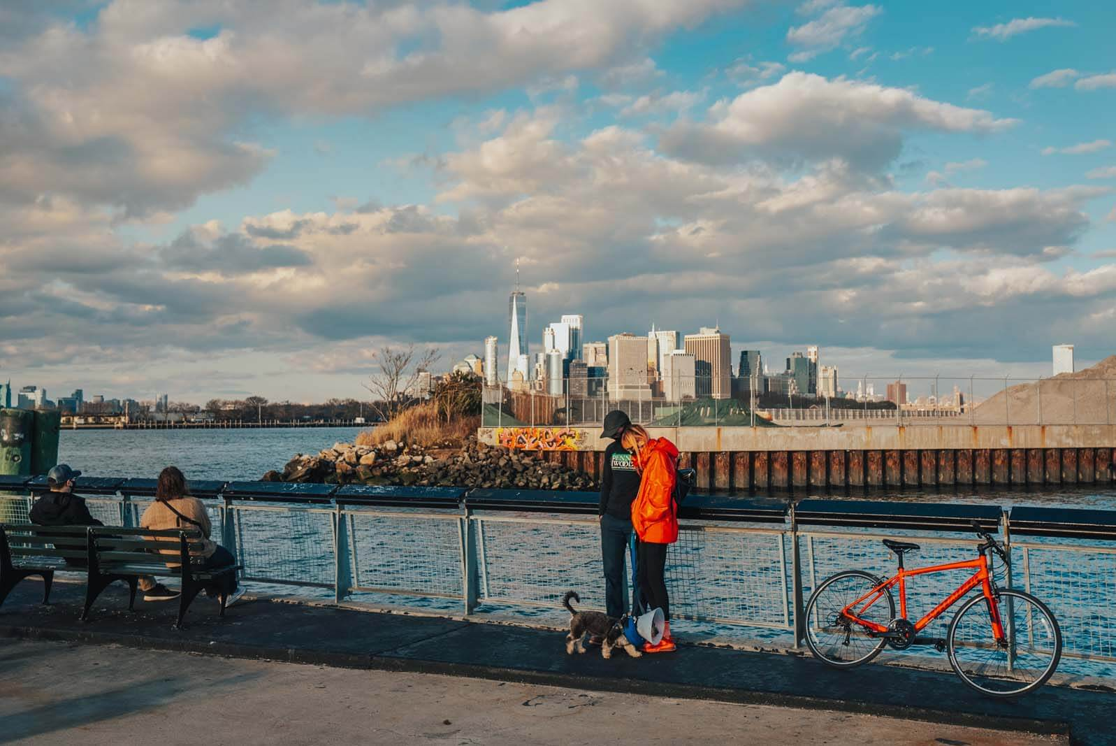 People Standing on the Pier at Louis Valentino Park with a Bench and Manhattan View