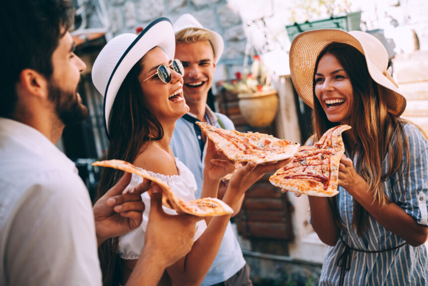 group-of-friends-laughing-at-hilarious-pizza-quotes-while-eating-a-slice-of-pizza