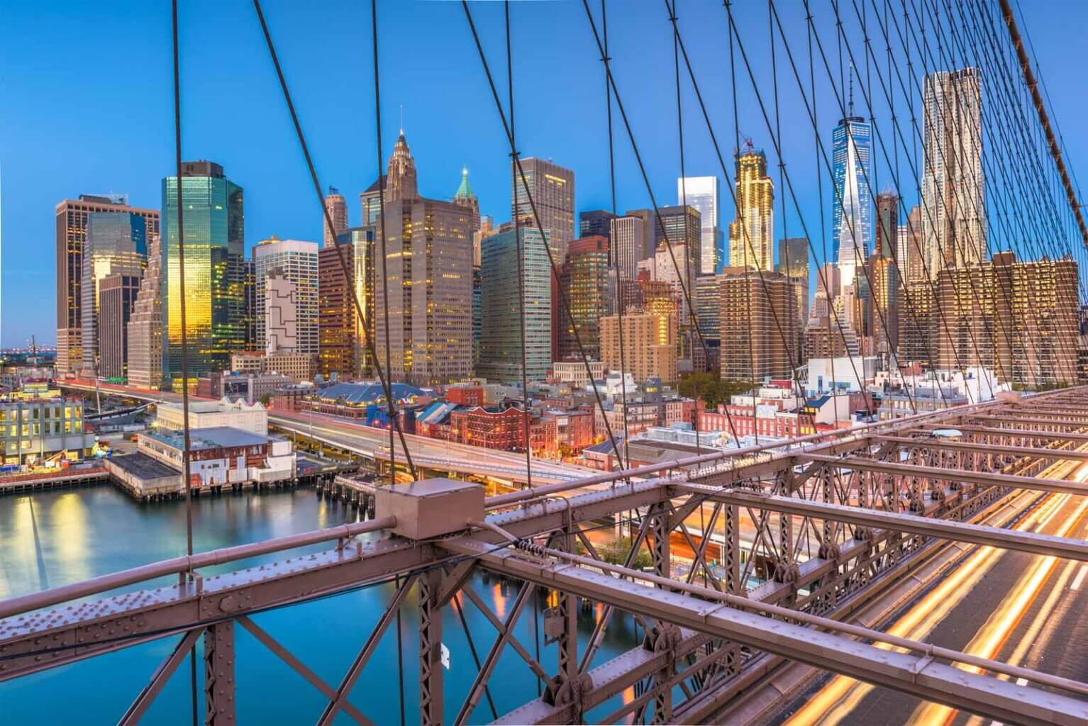 View of Brooklyn Bridge with Car Trails and Lower Manhattan Skyline at Sunset