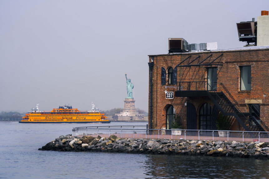 staten-island-ferry-next-to-statue-of-liberty-in-new-york-harbor-view-from-red-hook-brooklyn