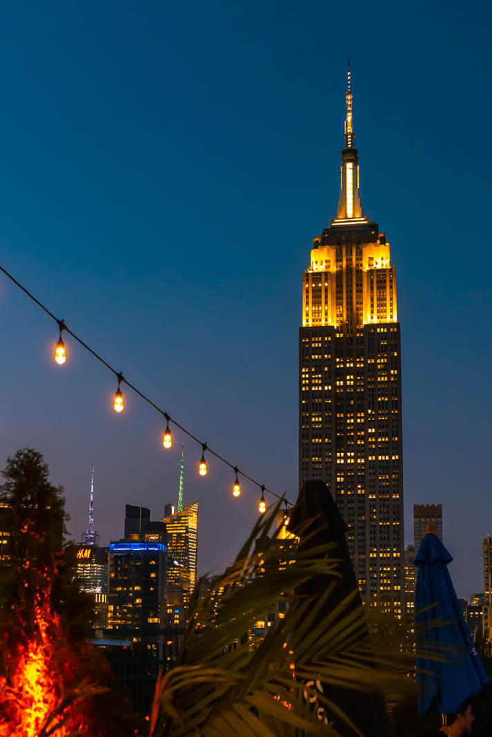 View of Empire State Building at night from 230 Rooftop in NYC