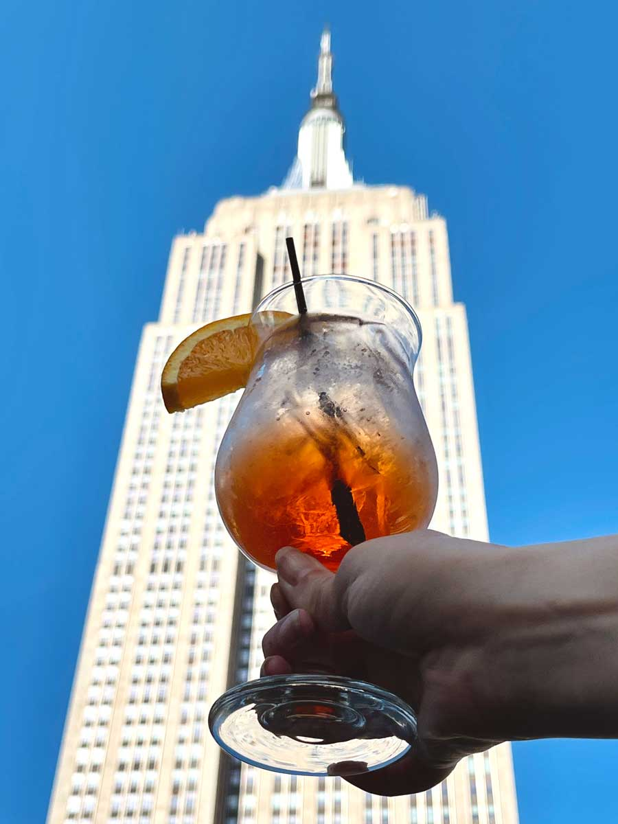 a-drink-at-cloud-9-social-rooftop-bar-in-nyc-with-view-of-the-empire-state-building-in-koreatown