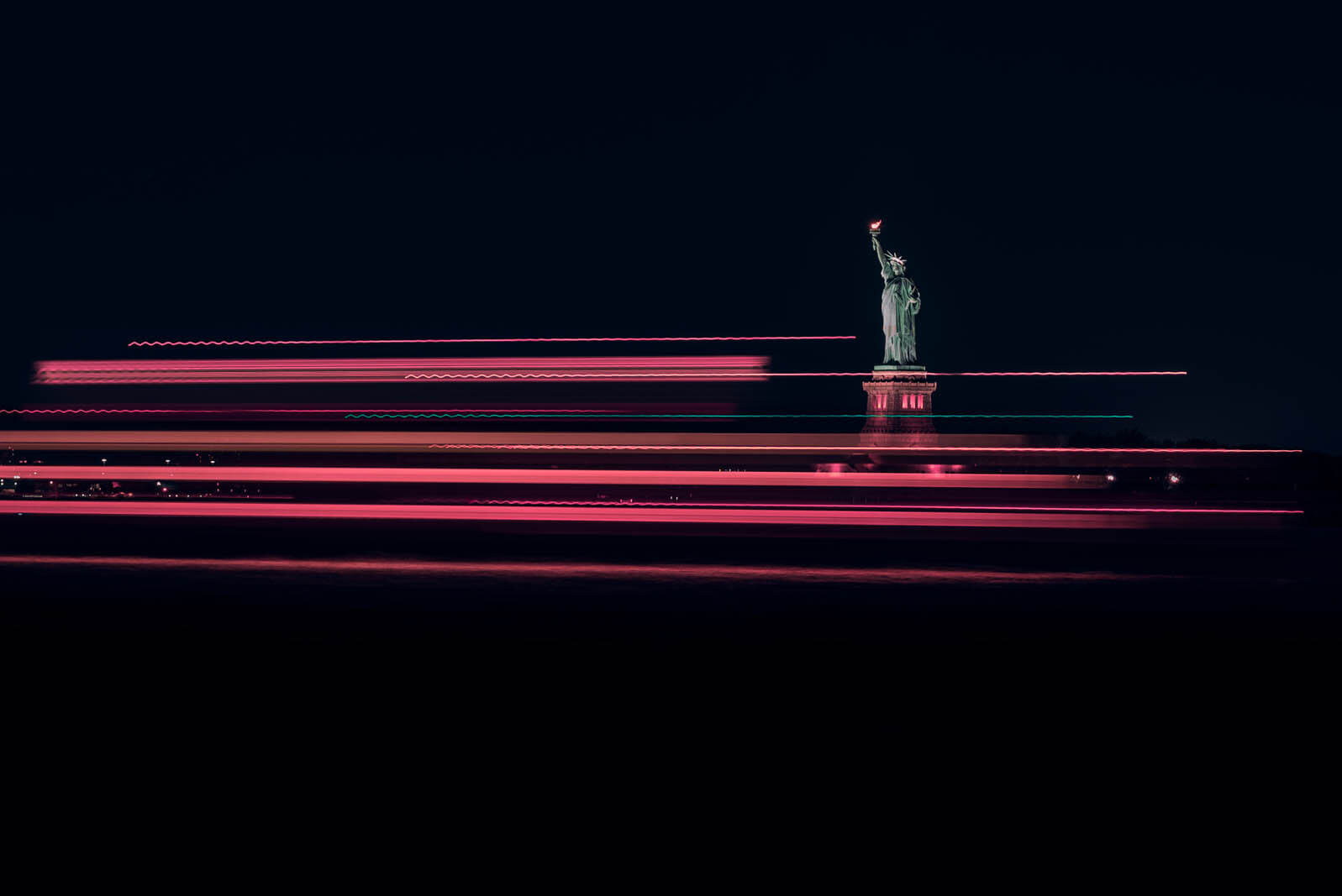 pink neon streaks from the boats passing the statue of liberty