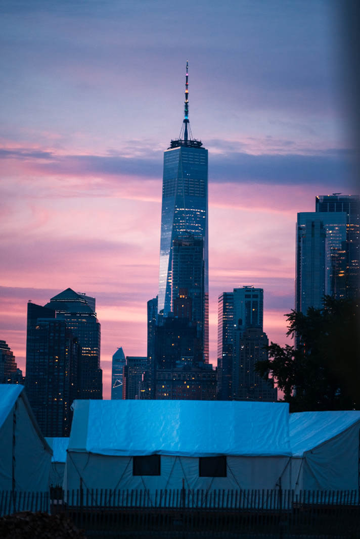 view of the World Trade Center from glamping at Collective Retreats Governors Island at sunset