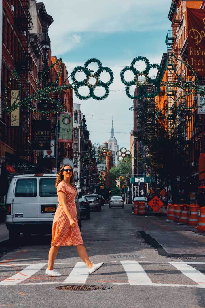 Megan walking through Little Italy with the Empire State Building in the backdrop in NYC
