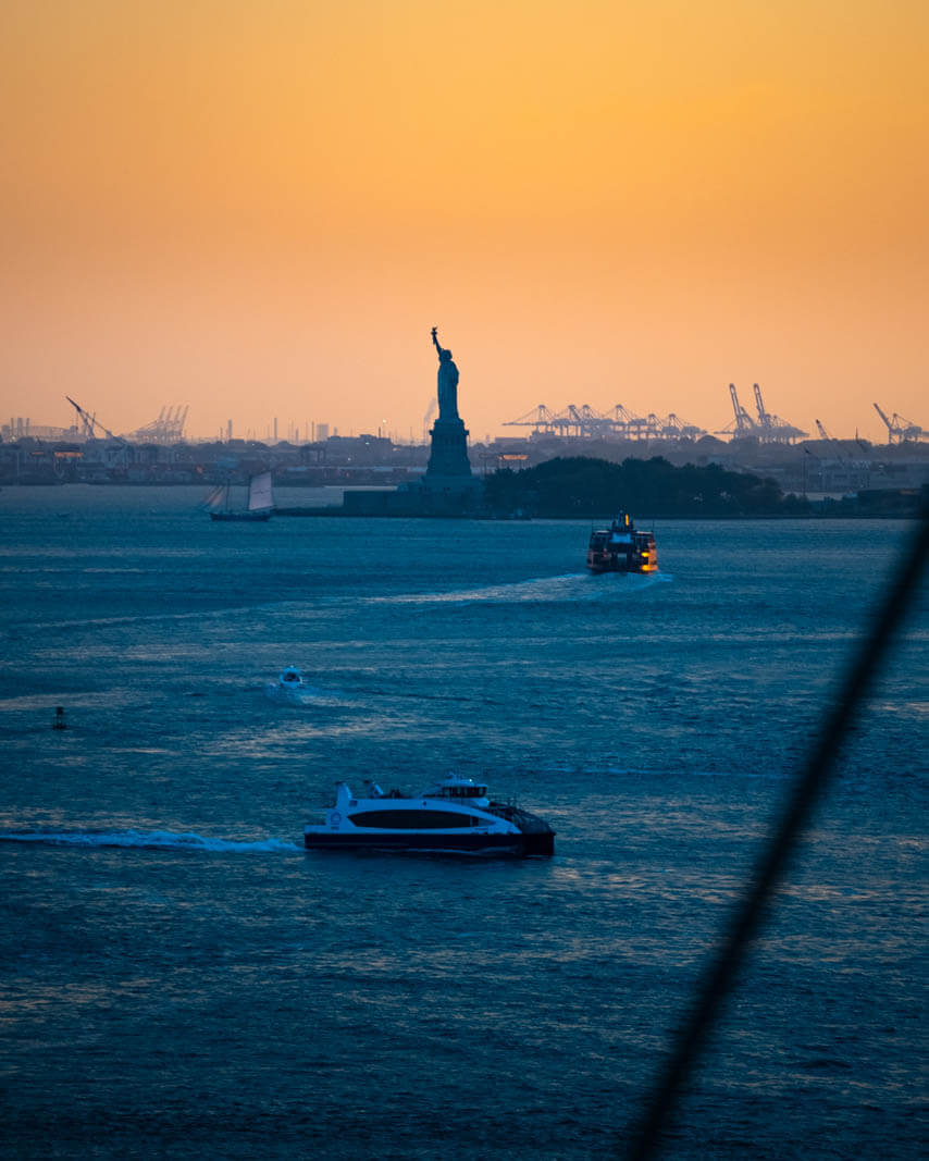 sunset view of the statue of liberty from the brooklyn bridge