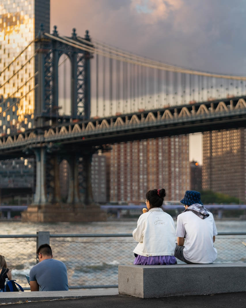 A couple eating Icecream in front of Jane's Carousel with the Manhattan Bridge in the background at Brooklyn Bridge Park in DUMBO
