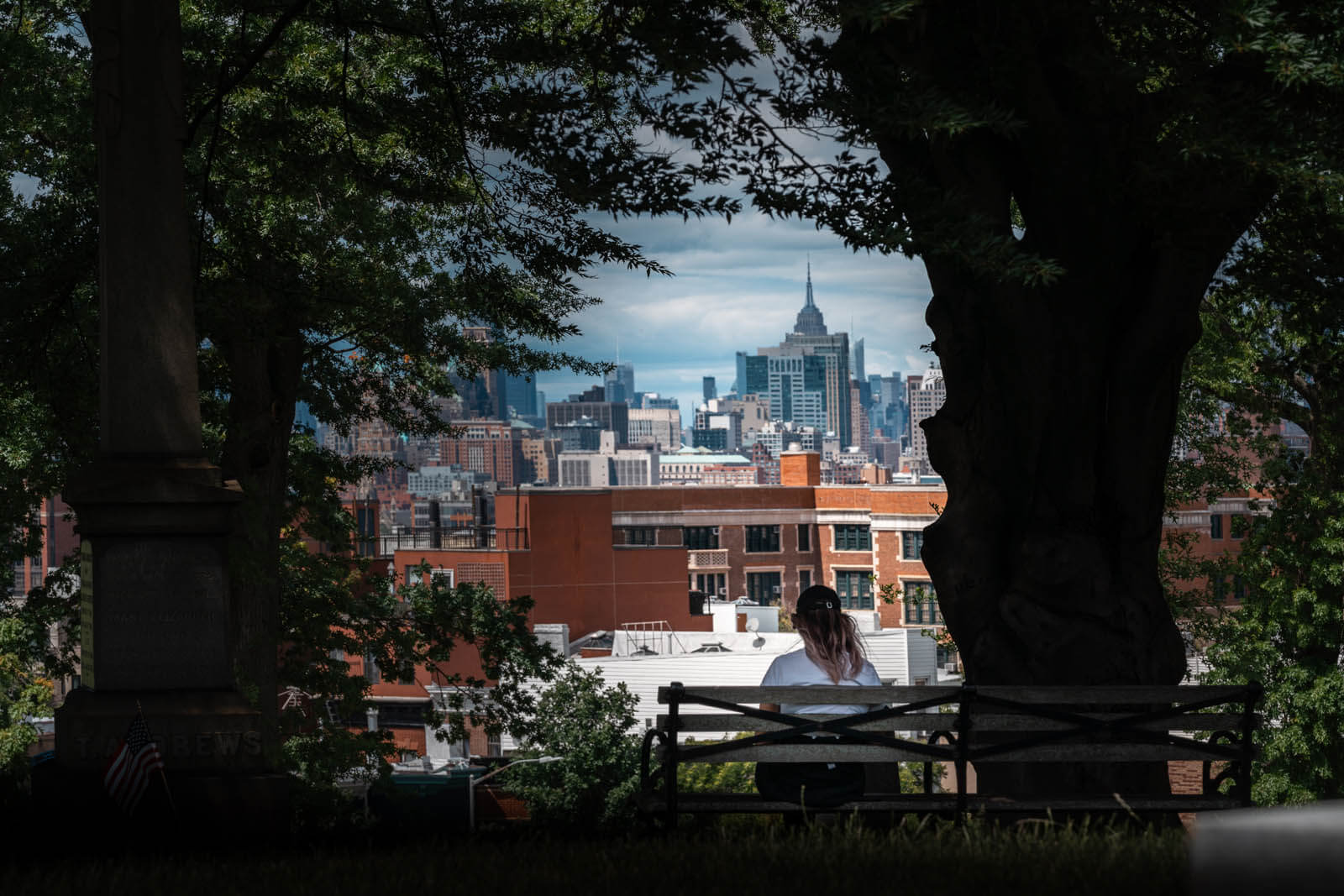 Megan sitting on Bench in Greenwood Cemetery with a view of the NYC skyline