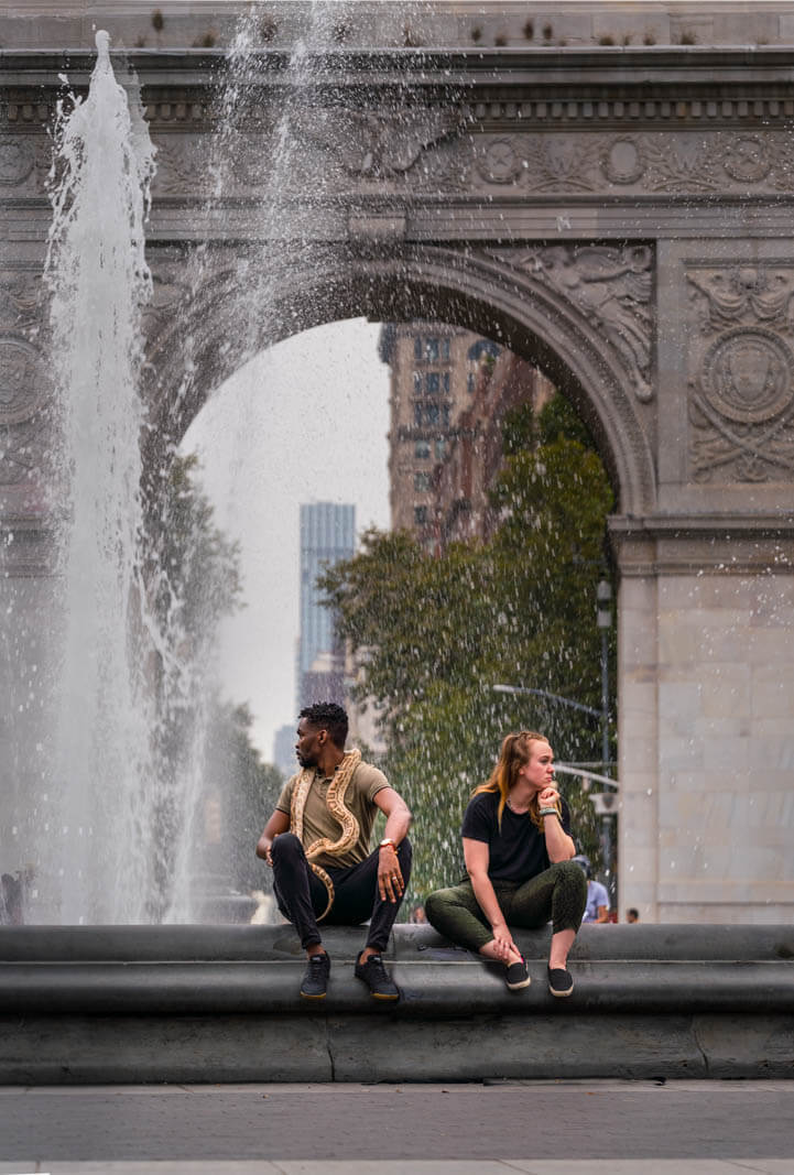 People watching at Washington Square Park in Manhattan a man with a snake at the fountain