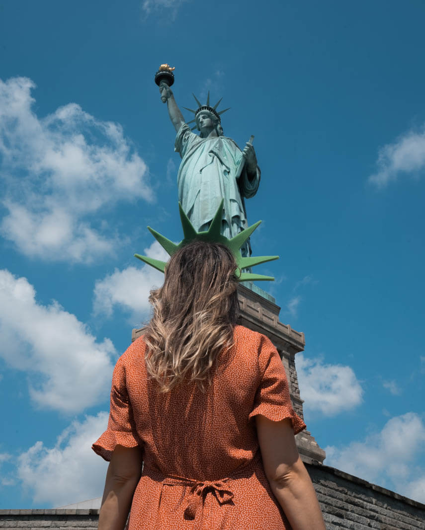 looking at the Statue of Liberty on Liberty Island wearing a lady liberty crown in NYC
