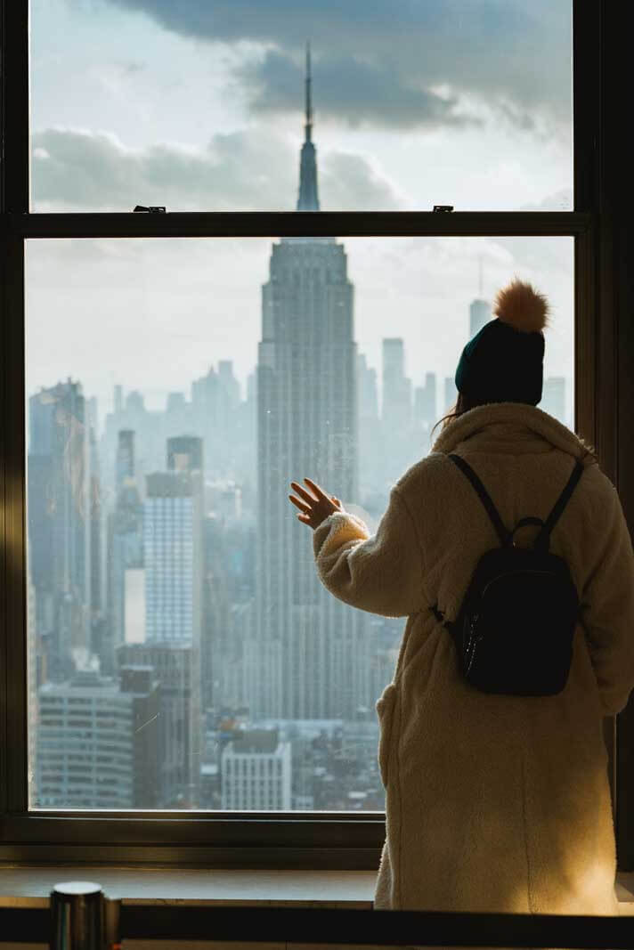 view of Empire State Building through the window at Top of the Rock in NYC